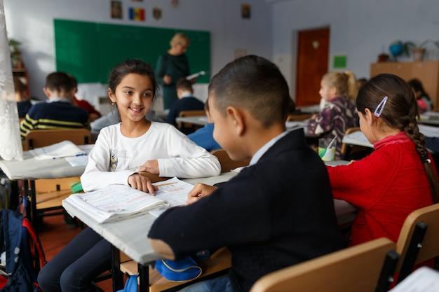 Uma garota com seus colegas resolvendo um problema matemático na escola