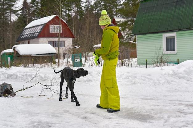 Uma garota com um agasalho de inverno veste dois cães de caça na floresta