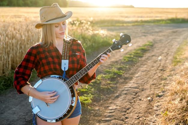 Uma garota com um banjo que fica em um campo sob o sol poente e canta uma música. estilo sertanejo. foco seletivo.