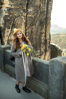 Uma garota com um casaco cinza e um chapéu com um buquê de flores no fundo das montanhas