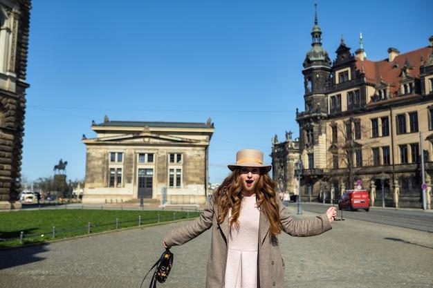 Uma garota com um casaco e um chapéu em uma rua da cidade de dresden. suíça saxônica, alemanha.