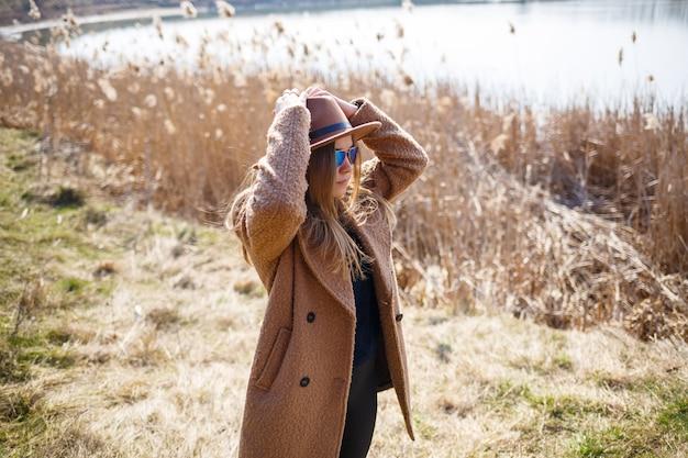 Uma garota com um casaco marrom, chapéu e óculos caminha em um parque com um lago sob o sol forte. alegra-se com a vida e sorri. o começo da primavera