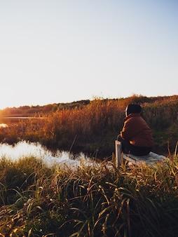 Uma garota com um casaco quente está sentada em um píer perto do lago e admira o pôr do sol no outono