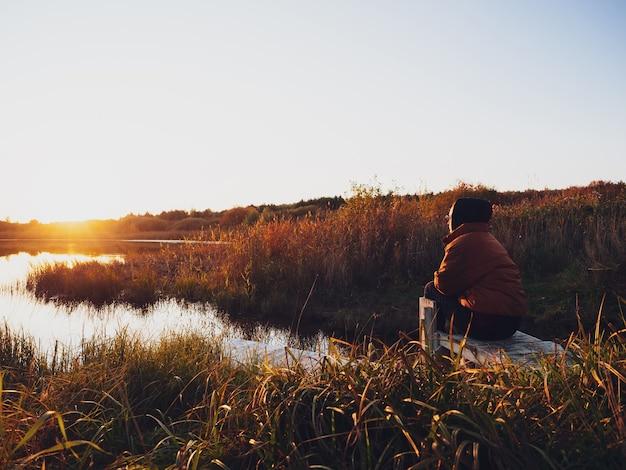 Uma garota com um casaco quente senta-se em um píer perto do lago e admira o pôr do sol no outono.