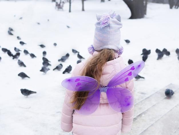 Uma garota com um casaco rosa e um chapéu rosa com asas roxas atrás das costas olha para os pombos