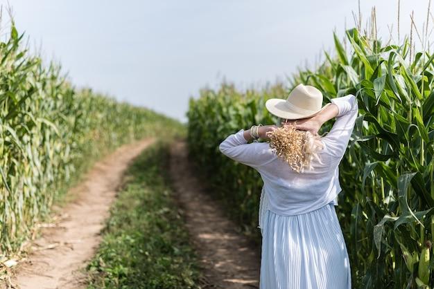 Uma garota com um chapéu de palha caminhando na plantação de milho
