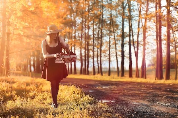 Uma garota com um chapéu em um passeio no parque. uma garota com uma cesta caminha no outono. menina está caminhando pela estrada ao pôr do sol.