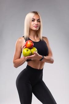 Uma garota com um corpo atlético perfeito segura maçãs nas mãos em um fundo cinza