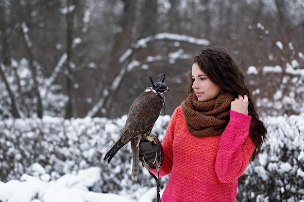 Uma garota com um falcão passeia no inverno na floresta