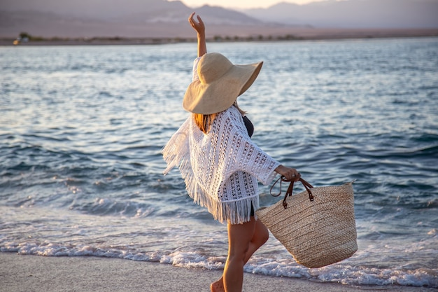Uma garota com um grande chapéu e uma bolsa de vime caminha ao longo da costa do mar. conceito de férias de verão.