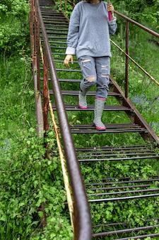 Uma garota com um guarda-chuva anda na floresta em tempo chuvoso com botas de borracha.