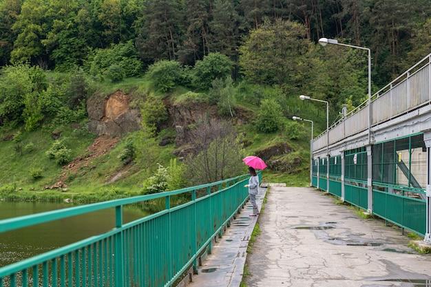 Uma garota com um guarda-chuva em tempo nublado para uma caminhada na floresta, fica em uma ponte contra o pano de fundo de uma paisagem.