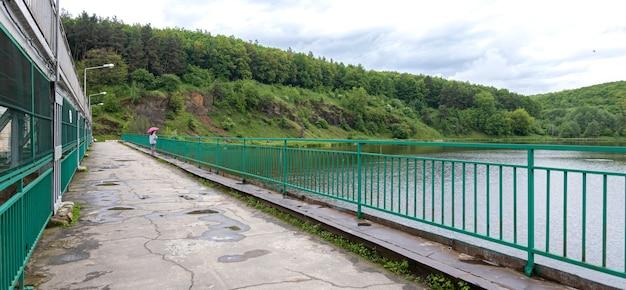Uma garota com um guarda-chuva em tempo nublado para uma caminhada na floresta fica em uma ponte, tendo como pano de fundo uma paisagem