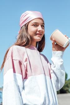 Uma garota com um lenço rosa na cabeça bebe um café. dia internacional do câncer de mama, com o céu ao fundo.