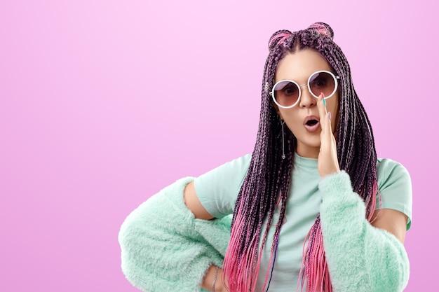 Uma garota com um penteado de tranças cor de rosa em roupas turquesa e óculos escuros sussurra algo para a câmera em confiança. o conceito é estilo moderno, individualidade, abrangência, criatividade.