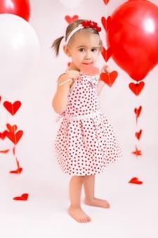 Uma garota com um pirulito no fundo de balões vermelhos e guirlandas em corações.