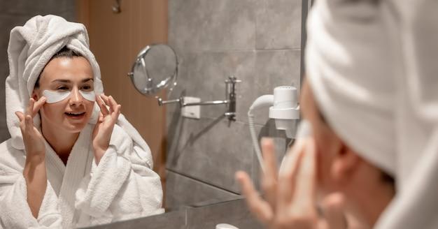 Uma garota com um roupão de banho e uma toalha na cabeça cola manchas sob os olhos no banheiro em frente ao espelho.