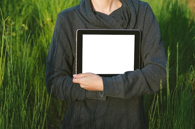 Uma garota com um suéter cinza tem uma maquete de tablet nas mãos. no contexto de uma bela natureza.