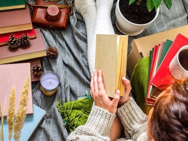 Uma garota com um suéter de tricô está rodeada por muitos livros antigos diferentes.