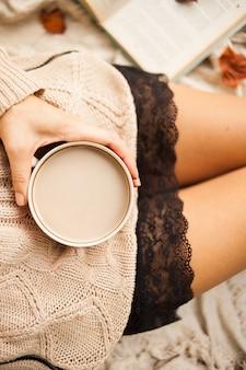 Uma garota com um suéter quente senta-se sobre um cobertor de lã bege e detém uma caneca de café quente nas mãos dela.