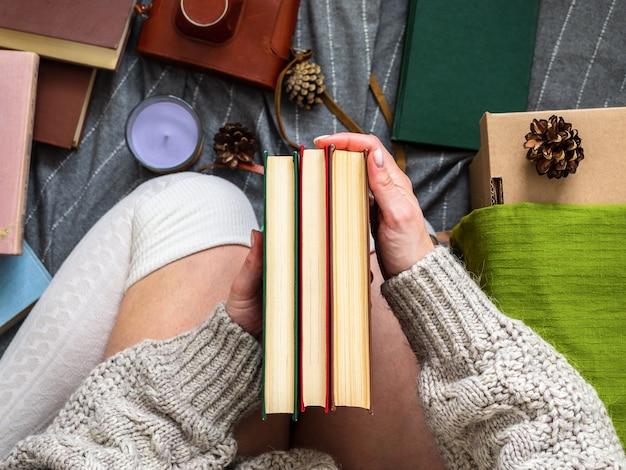 Uma garota com um suéter sem rosto está sentada em um cobertor com livros
