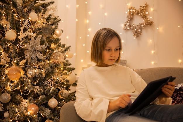 Uma garota com um tablet no sofá em uma sala de estar decorada de maneira festiva, foco suave