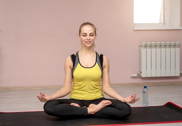 Uma garota com um uniforme esportivo em posição de lótus sentada na academia