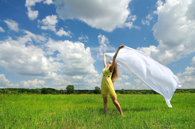 Uma garota com um vestido amarelo em um campo verde posa com as mãos e o rosto para cima