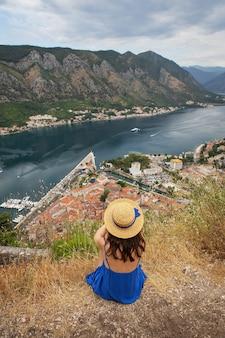 Uma garota com um vestido azul e um chapéu de palha se senta no cenário da baía de kotor