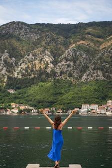 Uma garota com um vestido azul está de pé com as mãos no cais, tendo como pano de fundo a baía de kotor, em montenegro. cidade simpática e acolhedora.