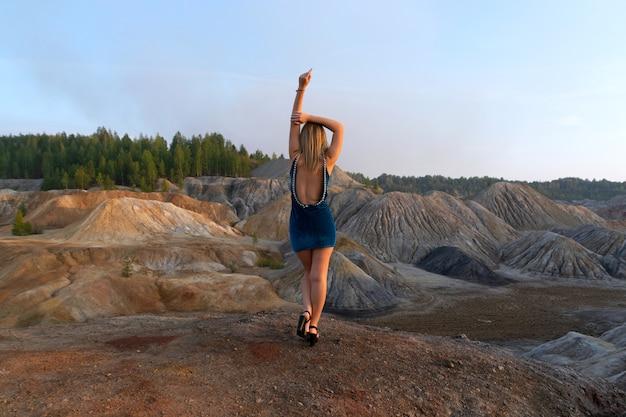 Uma garota com um vestido azul no topo de uma montanha. quarry e montanhas de argila