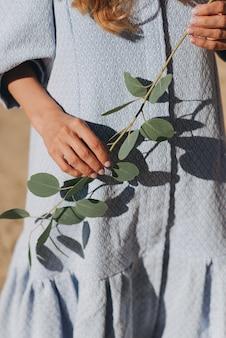 Uma garota com um vestido azul segura um galho de eucalipto verde nas mãos. folhas vivas