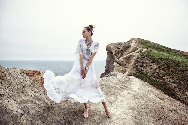 Uma garota com um vestido branco e enfeites em pé em um penhasco