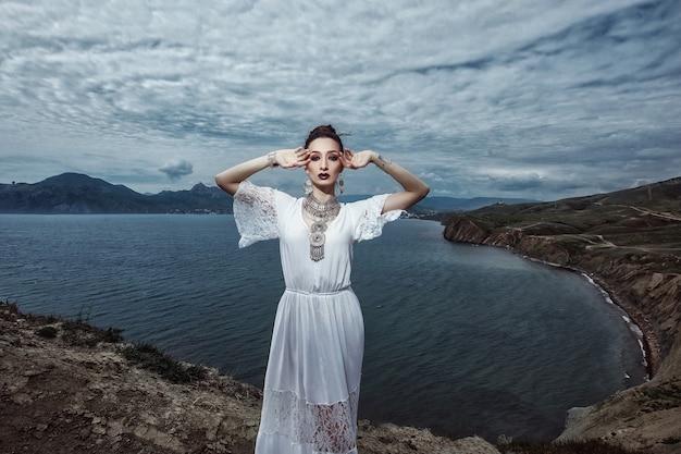 Uma garota com um vestido branco e joias está em um penhasco