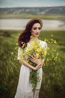 Uma garota com um vestido branco, um chapéu elegante com um buquê de flores amarelas