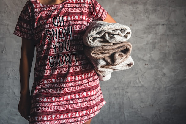 Uma garota com um vestido de natal segura uma pilha de suéteres. calor, conforto