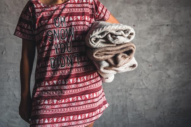 Uma garota com um vestido de natal segurando uma pilha de suéter