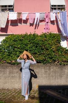 Uma garota com um vestido e um chapéu caminha à tarde em uma cidade italiana na toscana.