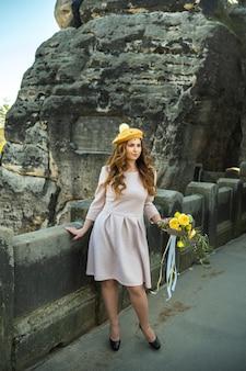 Uma garota com um vestido rosa e um chapéu com um buquê de flores no fundo das montanhas e desfiladeiros na saxônia suíça, alemanha, bastei