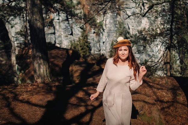 Uma garota com um vestido rosa e um chapéu no contexto das montanhas e desfiladeiros na saxônia suíça