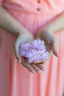 Uma garota com um vestido rosa tem uma flor de sakura nas mãos.