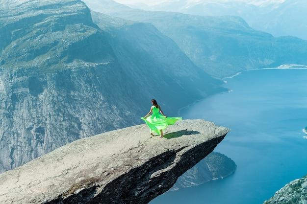 Uma garota com um vestido verde claro dança no trolltunga na noruega