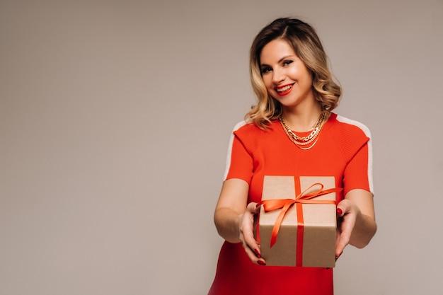 Uma garota com um vestido vermelho com presentes nas mãos em um fundo cinza