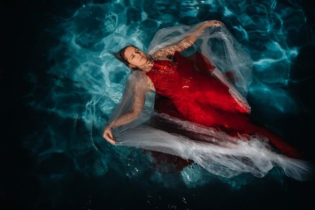 Uma garota com um vestido vermelho está flutuando na água. uma jornada na água de uma mulher solteira