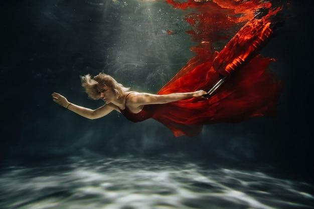 Uma garota com um vestido vermelho está flutuando sob a água com uma mala. viagem sob a água de uma mulher solteira. o conceito de turismo subaquático