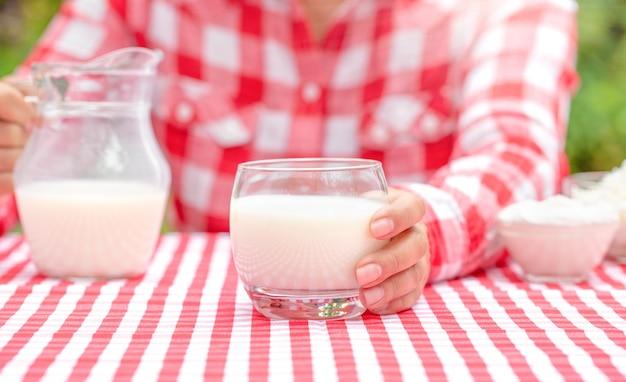 Uma garota com uma camisa xadrez vermelha segurando um copo de leite