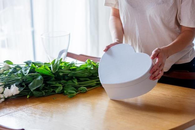 Uma garota com uma camiseta branca está segurando uma caixa de presente branca em forma de coração perto de um buquê de rosas brancas na mesa da cozinha. conceito de estilo de vida