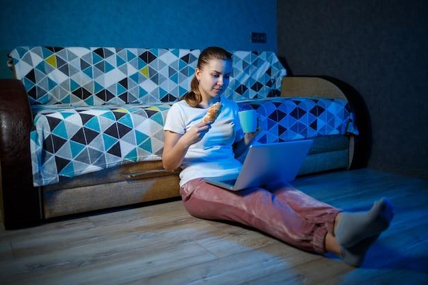 Uma garota com uma camiseta branca está sentada em casa no escuro no sofá e assiste a um filme em seu laptop. come um croissant e bebe chá