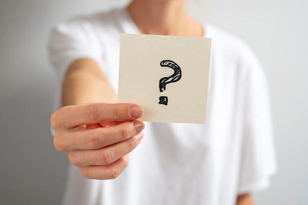 Uma garota com uma camiseta branca segura um adesivo de papel com um ponto de interrogação na mão. concentre-se na etiqueta, fundo desfocado.