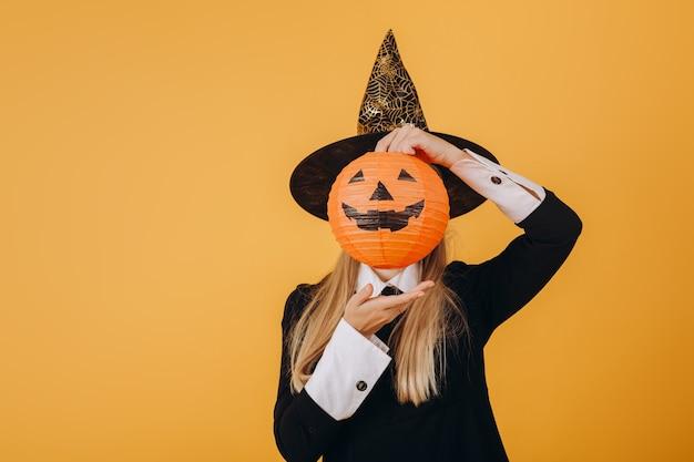 Uma garota com uma fantasia de halloween segura uma abóbora em volta do rosto. foto de alta qualidade